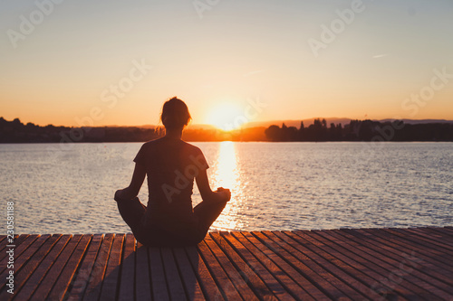 yoga, woman doing meditation and breathing exercises on wooden pier near lake, silhouette at sunset