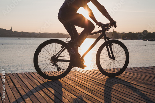 La pose en embrasure Cyclisme man riding bicycle at sunset, cycling in summer, silhouette of cyclist near the lake
