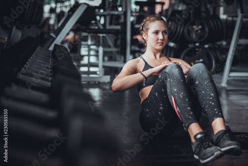 Fotografie, Obraz  Cinematic tone of young attractive fitness woman exercise with machine in gym