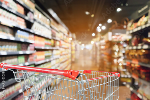 Fotografía  supermarket aisle blurred background with empty red shopping cart
