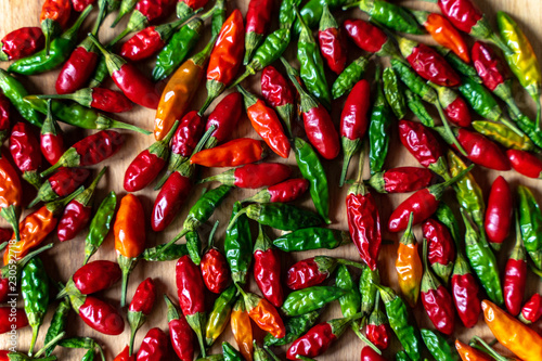 Fotografia  Colorful Chilli Peppers On Wooden Table. High Angle View Close Up