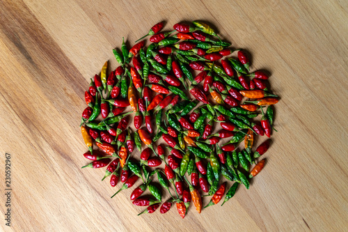 Fotografia  Colorful Chilli Peppers On Wooden Table. High Angle View