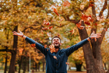 Young Man Throwing Autumn Leav...