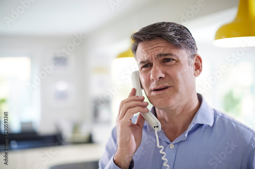 Frustrated Mature Man Receiving Sales Call At Home
