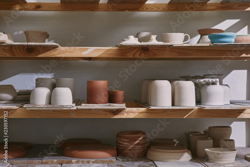 Canvas Print ceramic bowls and dishes on wooden shelves at pottery studio