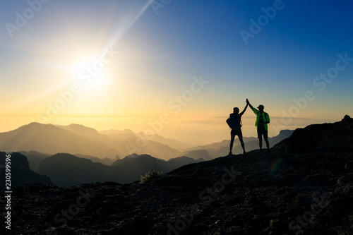 Spoed Foto op Canvas Grijze traf. Couple hikers celebrating success concept in mountains