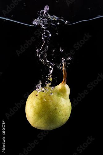 Pear splashing in water on black