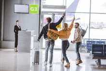 Back View Of Happy Young Friends Waving Hands And Going To Check-in Desk In Airport