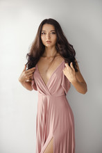 Portrait Of Beautiful And Young Bridesmaid In Pink Dress Indoors Agaist Gray Wall In Studio. Adorable Girl With Perfect Make-up And Hair Style Looking In Camera. Gorgeous Slim Mixed Race Caucasian