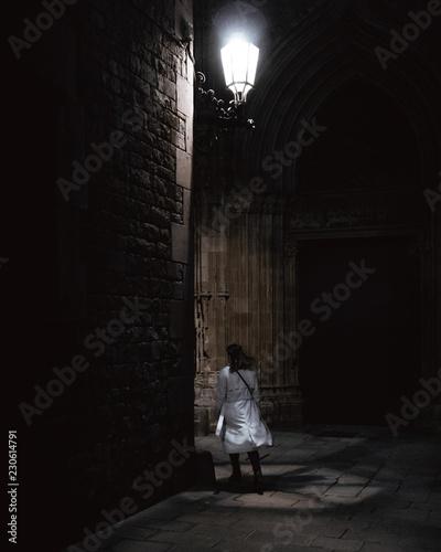 Fotografija  Una mujer con abrigo anda debajo de una farola por la noceh.