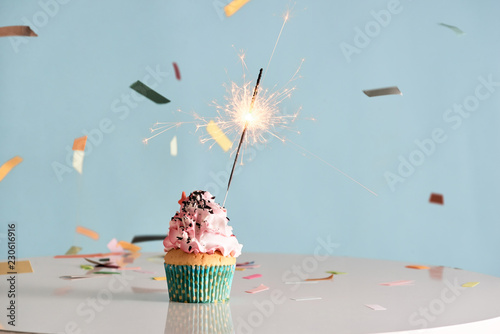 Photo  Single sparkler on cupcake blue wal
