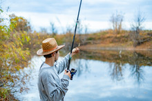 Young Man In Hat Sitting Near Lake And Install Set Up And Adjust Fishing Rod  F