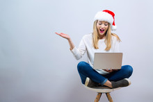 Young Woman With Santa Hat Using Her Laptop On A Gray Background