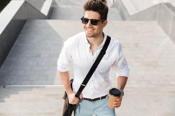 Fototapeta Confident businessman dressed in shirt walking upstairs