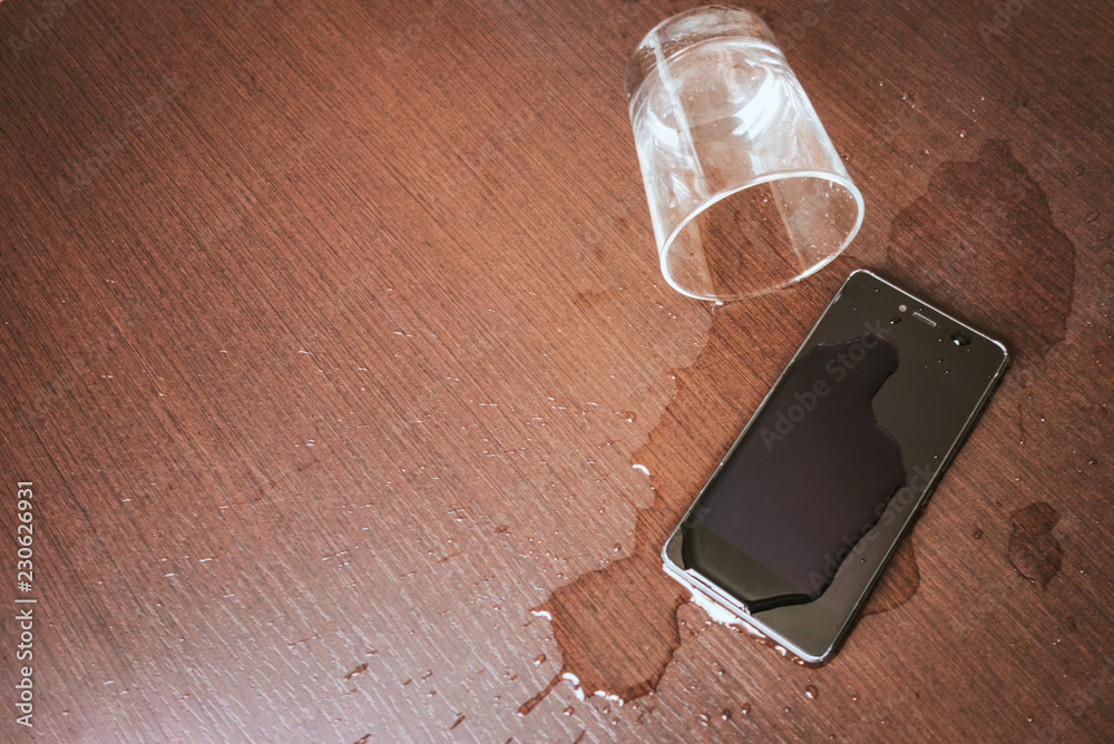 Fototapeta Smartphone wet by accident on wooden table. Glass of water spilled.