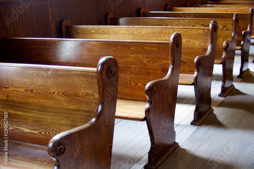Carved Wooden pews in church in sunshine Fototapet