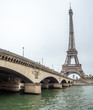 View of the Eiffel Tower From the River Next to Large Bridge