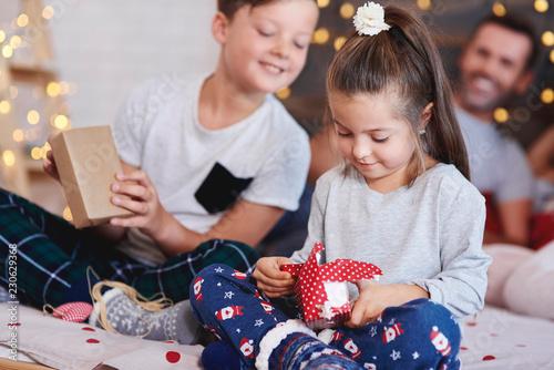 Fotografia, Obraz  Adorable girl opening christmas present in bed
