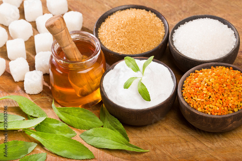 Variety of sweeteners - Stevia, sugar, pollen and honey. Wood background