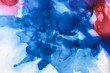 beautiful blue, red and violet splashes of alcohol inks as abstract background