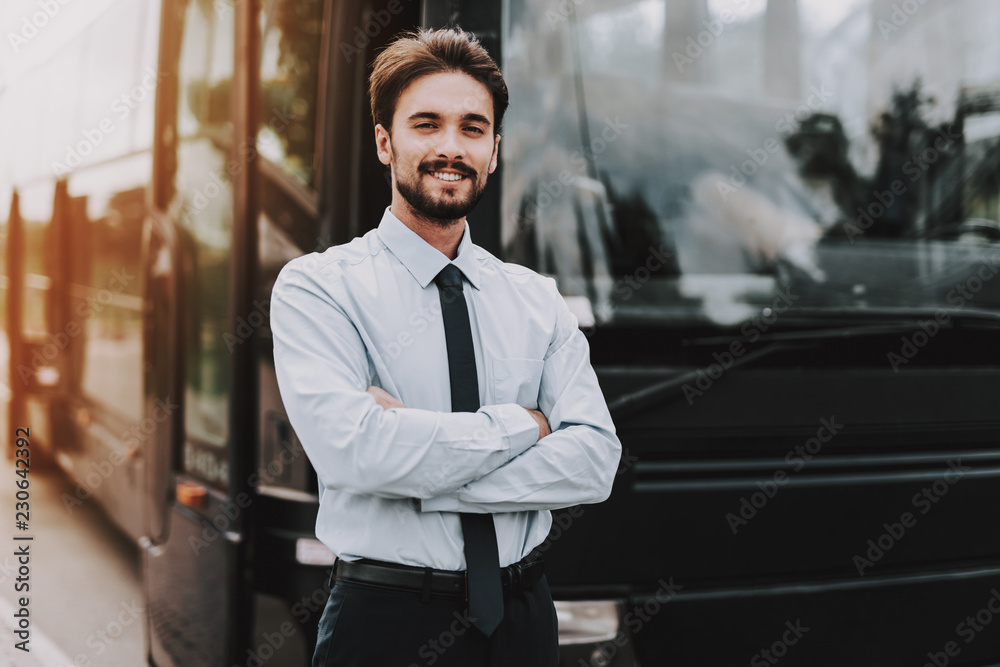 Fototapeta Young Smiling Businessman Standing in front of Bus