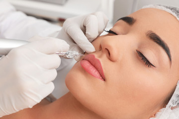 Young woman undergoing procedure of permanent lip makeup in tattoo salon, closeup