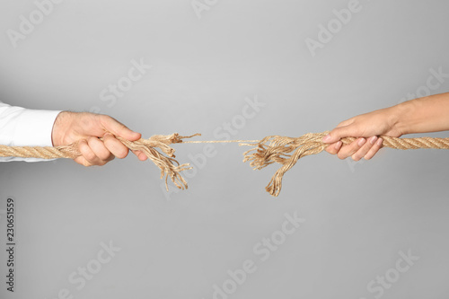 Cuadros en Lienzo Man and woman pulling frayed rope at breaking point on gray background