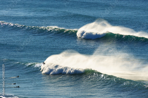 waves spraying and surfers on the sea