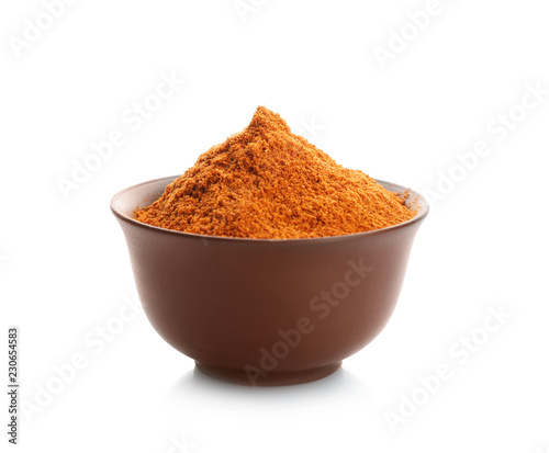 Bowl with red pepper powder on white background