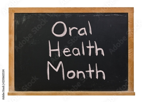 Fotografie, Obraz  Oral Health Month written in white chalk on a black chalkboard isolated on white