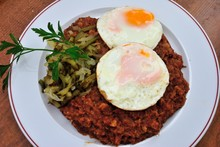 """Traditional Bremen Style """"Seemannslabskaus"""" Made Of Corned Beef And Mashed Potatoes With Two Fried Eggs, And Strips From Gherkin"""