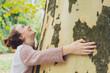 Leinwanddruck Bild - Laughing happy young woman hugging a tree