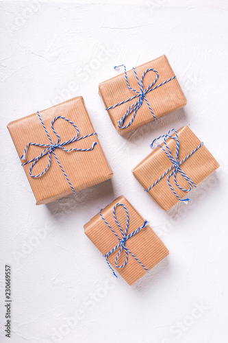 Festive gift boxes with presents on textured white wooden background.
