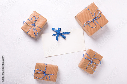 Empty tag and wrapped gift boxes with presents on textured background