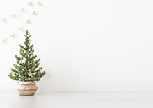 Interior White Wall Mock Up With Decorated Christmas Tree In Basket And Flag Garland On Empty Background. 3D Rendering.