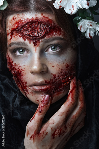 Portrait of bloody horrible scary zombie girl in a halloween festive makeup.