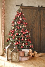 Interior. Beautiful Christmas Tree Decorated With Red Balls And Toys. Vertical Photo. Under The Tree Are Gifts And Vintage Lanterns. The Atmosphere Of Celebration And Comfort. Christmas Card