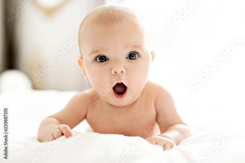 Obraz A Cute baby girl on a white bed at home yawn - fototapety do salonu
