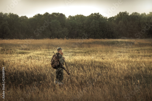 Poster de jardin Chasse hunter hunting in rural field nearby woodland at sunset during hunting season