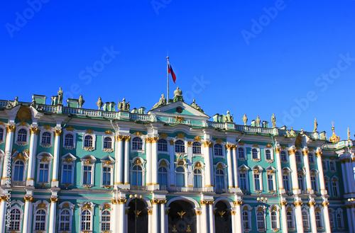 Poster Artistique Winter Palace Building at Palace Square in Saint Petersburg, Russia. Facade of Winter Palace with Russian Flag, Old Historic City Landmark on Empty Blue Sky Background on Sunny Summer Day