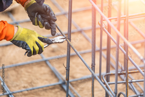 Fotografia Worker Securing Steel Rebar Framing With Wire Plier Cutter Tool At Construction