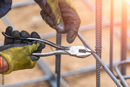 Carta da parati Worker Securing Steel Rebar Framing With Wire Plier Cutter Tool At Construction