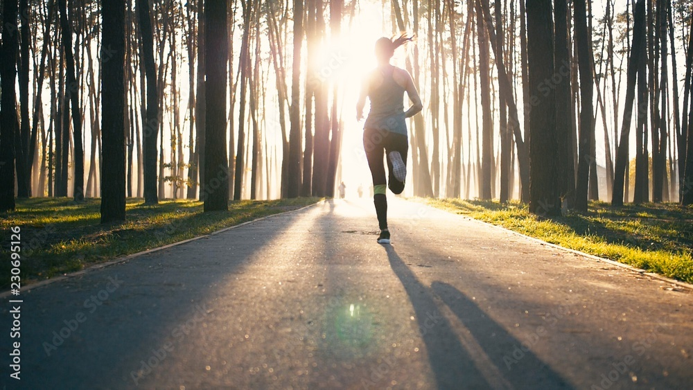 Fototapety, obrazy: Young and slim woman run. Girl is jogging very fast. She dissapears in lights of morning sun