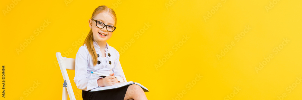 Fototapeta Girl with red hair on a yellow background. A charming girl in transparent glasses sits on a white chair and makes notes in a notebook.