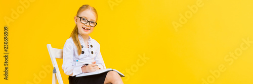 Obraz Girl with red hair on a yellow background. A charming girl in transparent glasses sits on a white chair and makes notes in a notebook. - fototapety do salonu