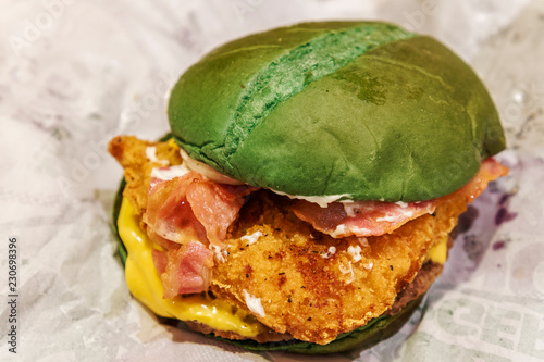 Halloween nightmare burger, as served. Green bun filled with ground beef burger, crispy chicken, bacon, American cheese and mayonnaise, advertised as increasing the chance of having nightmares.