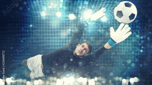Photo  Close up of a goalkeeper dives to save a shot aimed at the goal with light effec