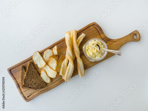 Israeli moussaka with bread chips on a board on a white table.