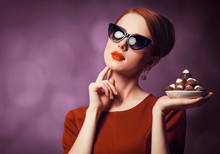Redhead Woman With Candy On Violet Background.