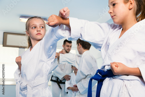Pair of little girls practicing new karate moves during class